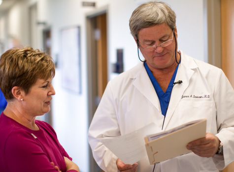 Dr. James Davison, Wolfe Eye Clinic LASIK surgeon, discusses LASIK candidacy evaluation results with nurse in Iowa.