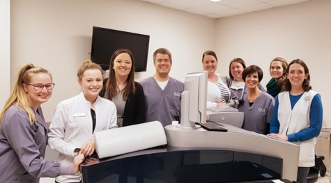 Wolfe Eye Clinic LASIK specialty team and Dr. Matthew Rauen stand next to all-laser LASIK technology in Des Moines, Iowa.