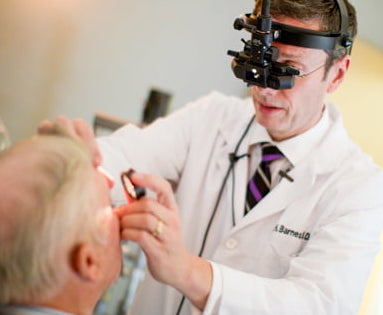 Wolfe Eye Clinic retina specialist, Dr. Charles Barnes, examines patient for retina disease in Cedar Rapids, Iowa.