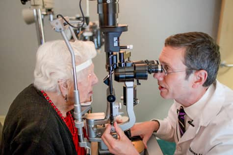 Iowa AMD retina specialist, Dr. Charles Barnes, examining patient's eyes.