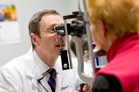 Iowa macular hole retina specialist, Dr. Charles Barnes, examines eyes of patient who may have a macular hole in the retina.